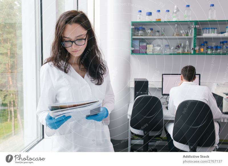Woman with papers in lab Laboratory Work and employment Science & Research Paper Human being