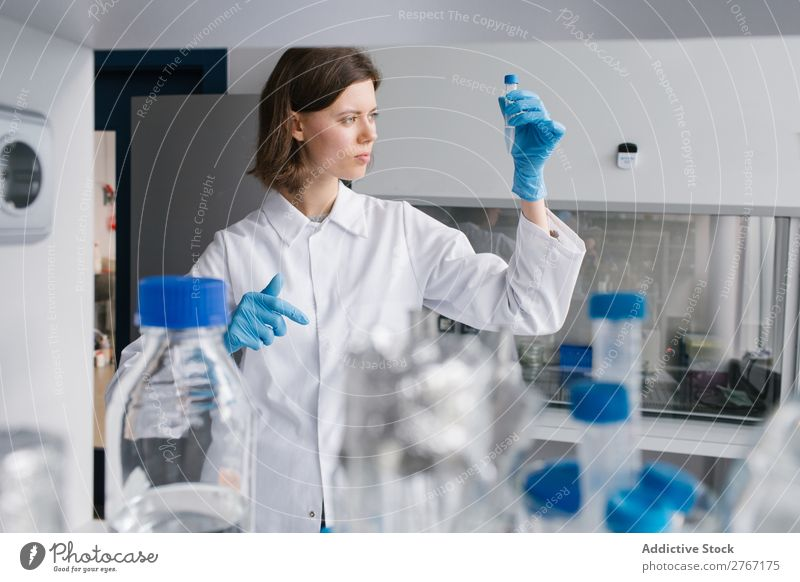 Worker looking at test tube Laboratory Work and employment Science & Research Woman Test tube Liquid Putt Human being