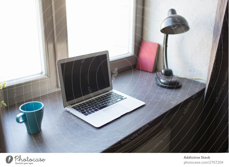 Laptop at window Notebook Cup Lamp Window Workplace Office Coffee Computer Desk Home House (Residential Structure) Business Screen desktop Table workspace