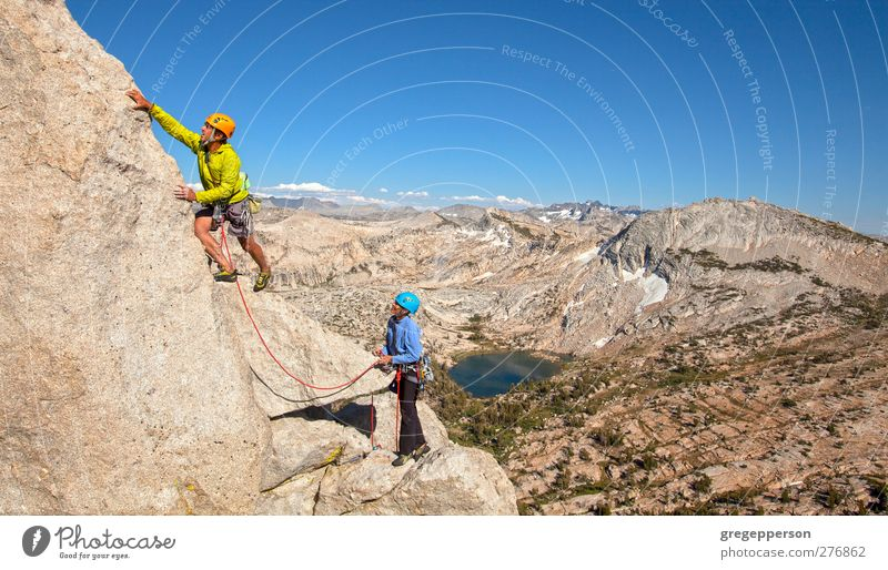 Climbing a challenging mountain. Life Adventure Mountaineering Success Rope Friendship Couple Partner 2 Human being 30 - 45 years Adults Rock Peak Helmet