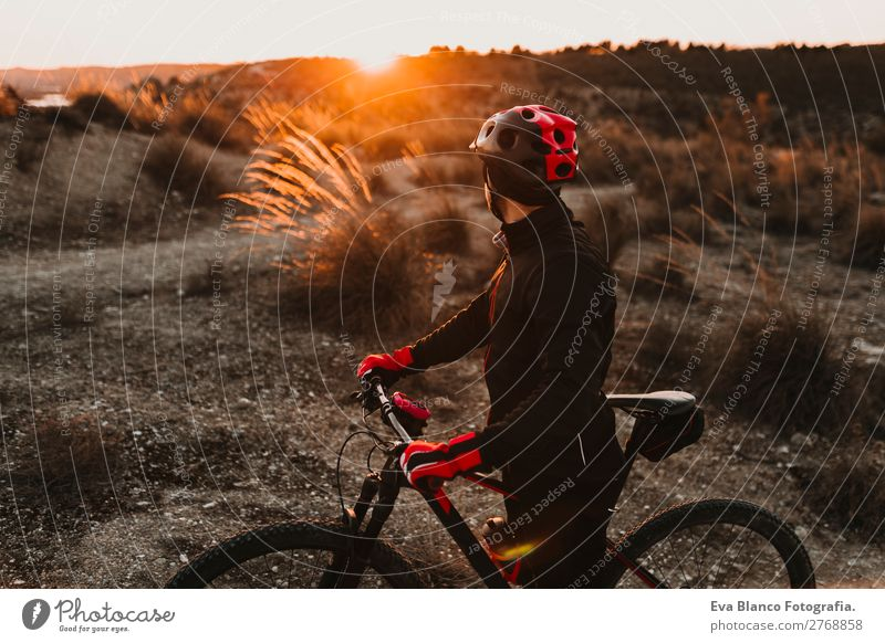 Cyclist Riding the Bike at Sunset. Sports Concept Human being Sky Nature Youth (Young adults) Man Summer Young man Landscape Red Relaxation Joy Winter Mountain
