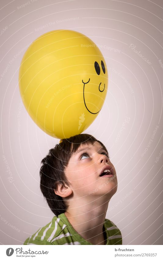 Child with balloon Leisure and hobbies Head Face 1 Human being Sign Select Observe Touch Throw Simple Elegant Happiness Yellow Balloon Laughter Smiley Looking