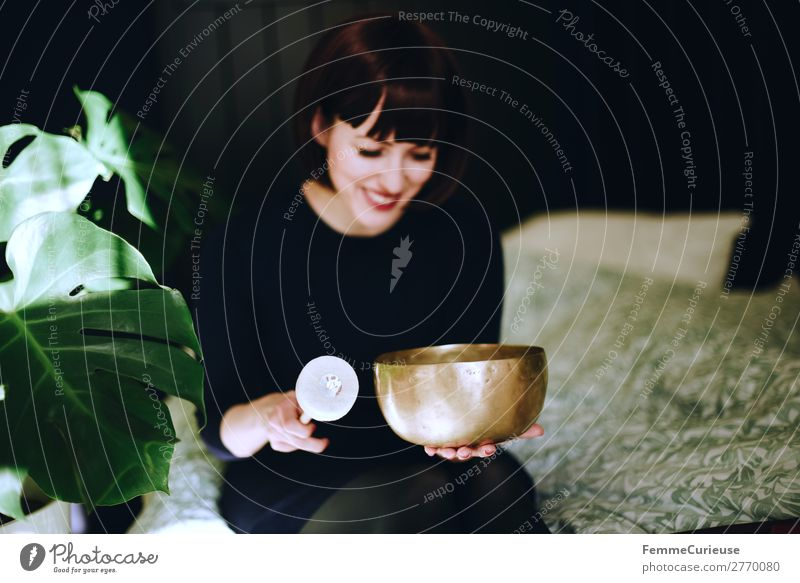 Mindfulness - Woman with singing bowl in her cozy home Healthy Life Harmonious Well-being Contentment Senses Relaxation Calm Meditation Feminine Adults 1