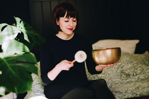Mindfulness - Woman with singing bowl in her cozy home Healthy Harmonious Well-being Contentment Senses Relaxation Calm Meditation Feminine Adults 1 Human being