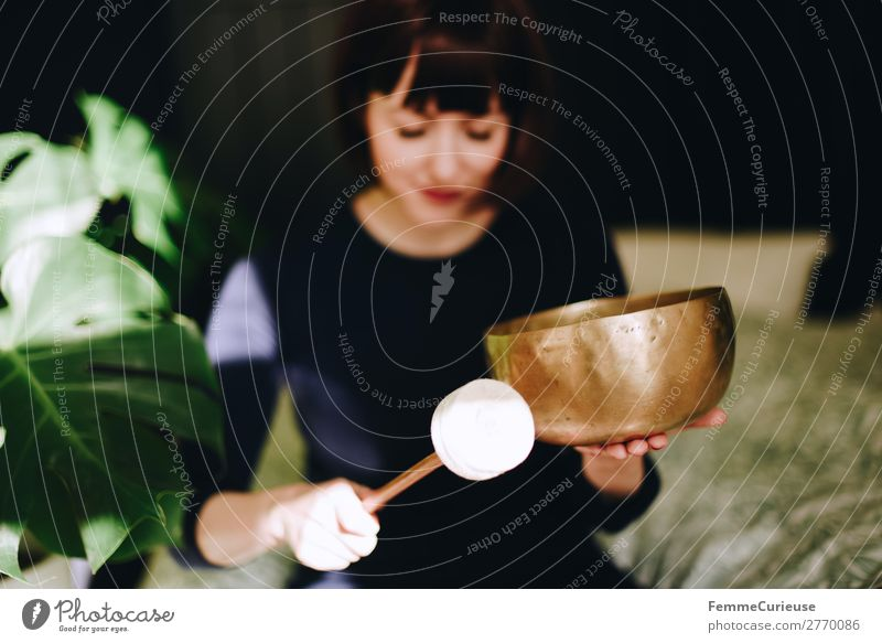 Mindfulness - Woman with singing bowl in her cozy home Harmonious Well-being Contentment Senses Relaxation Calm Meditation Feminine Adults 1 Human being
