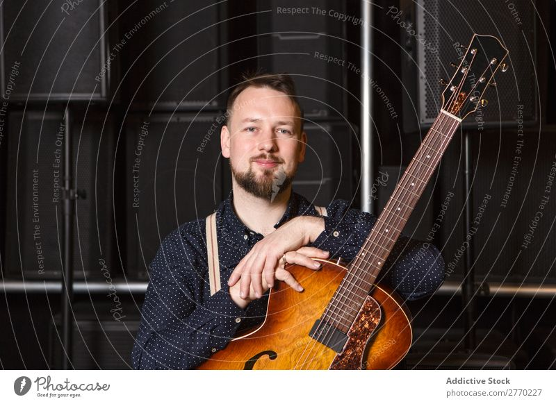 Guitarist sitting on guitar combo Man Shopping Looking into the camera seller Customer rows Musical Acoustic Equipment Human being Business Portrait photograph