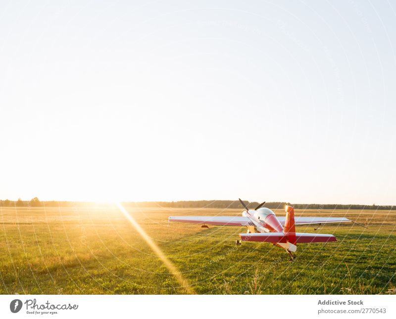 Shiny red airplane in green field Airplane Airfield Summer Transport Vacation & Travel Story Sunlight aerodrome Tourism Trip Glittering Technology Departure