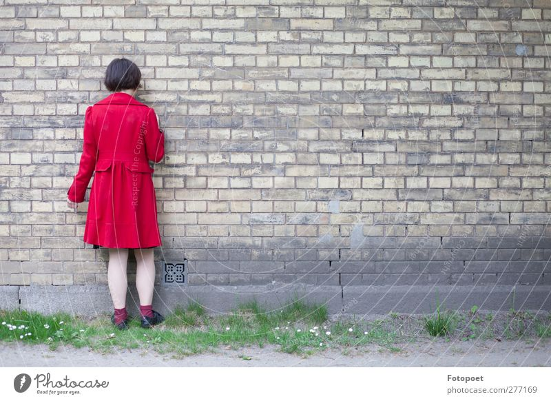 against the wall Feminine Young woman Youth (Young adults) 1 Human being 18 - 30 years Adults Wall (barrier) Wall (building) Coat Black-haired Touch Stand Red