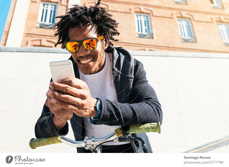 Afro young man using mobile phone and fixed gear bicycle. Man Youth (Young adults) African Black mulatto Mobile Bicycle fixie Telephone Lifestyle Stand Cycling