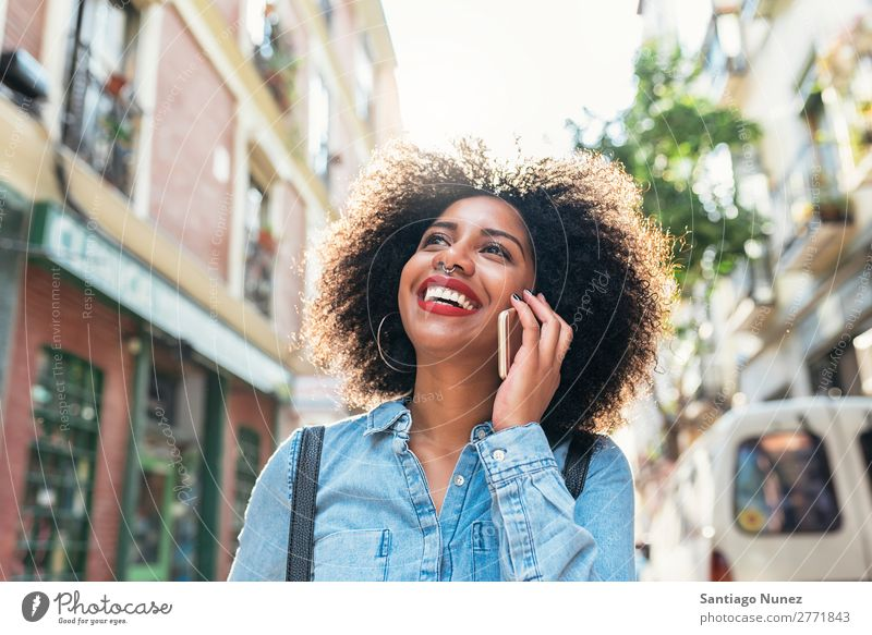 Beautiful afro american woman using her mobile in the street. Woman Black African Afro Human being Portrait photograph PDA Youth (Young adults) Mobile Telephone