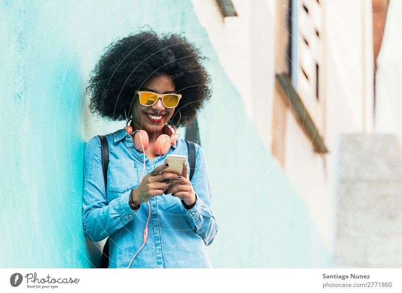 Beautiful afro american woman using mobile in the street. Woman Black African Afro Human being Portrait photograph PDA Youth (Young adults) Mobile Telephone