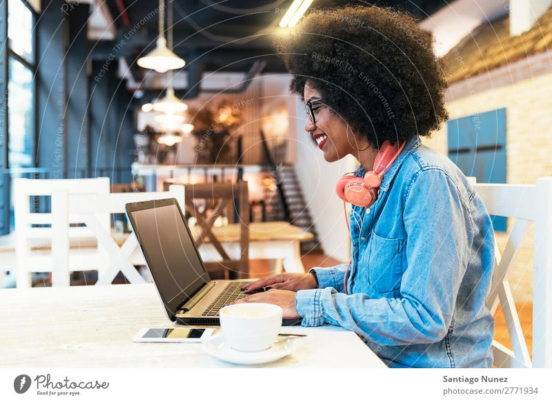 Beautiful afro american woman using mobile and laptop in the coffee shop. Woman Black African Afro Business Coffee Businesswoman Cellphone Youth (Young adults)