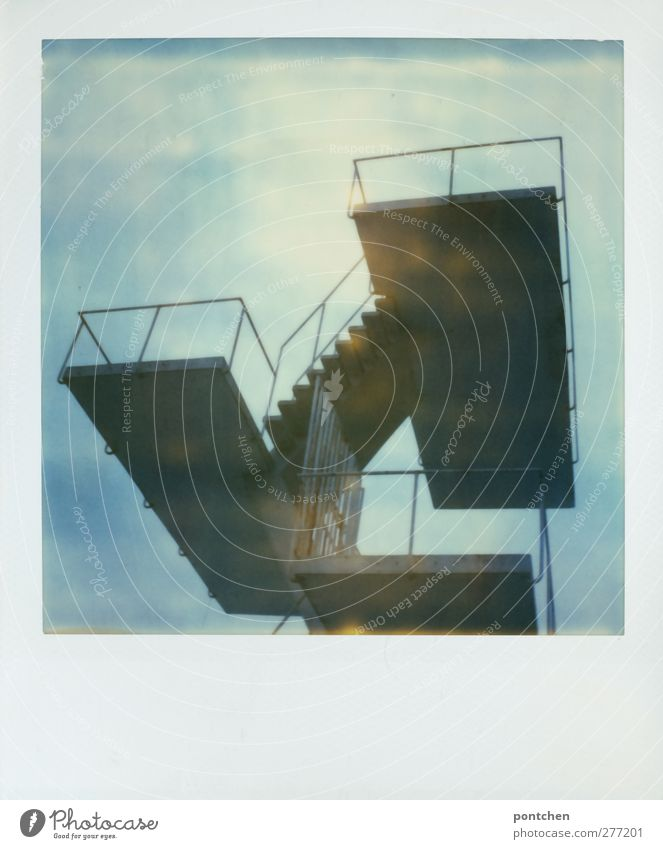 Polaroid shows diving platform in front of blue sky Moody Springboard Platform Stairs Sky Blue high Open-air swimming pool Banister Colour photo Subdued colour