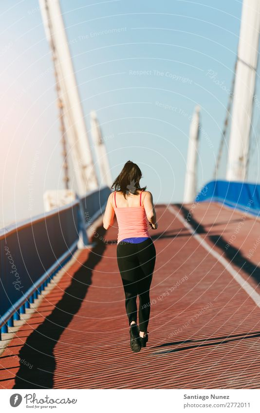 Young fitness woman runner running on city bridge. Running Runner Action Athlete Athletic Railroad Fitness Woman workout Practice Sports Strong Body Effort