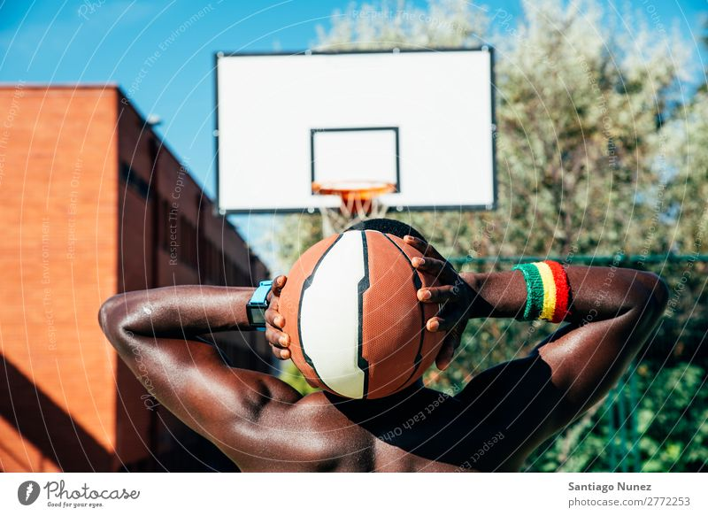 Male basketball player holding a ball. Action African-American Back Rear view Ball Basket Basketball Black City City life Court building Day Practice Playing