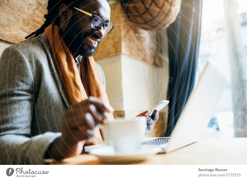 Businessman using his laptop in the Cofee Shop. Man Black African American Cellphone Youth (Young adults) Notebook Computer coffe shop Coffee Office Human being