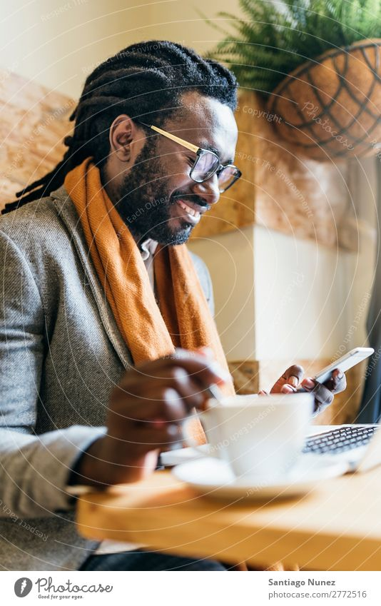 Businessman using his laptop in the Cofee Shop. Man Black African American Cellphone Youth (Young adults) Notebook Computer Happy Office Human being
