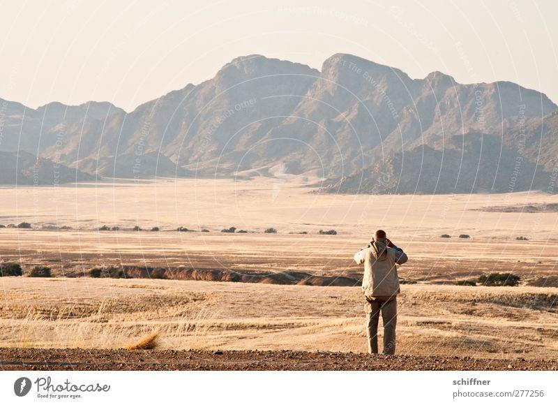 Human being Nature Man Loneliness Landscape Far-off places Environment Mountain Grass Freedom Rock Masculine Stand Peak Desert Grassland