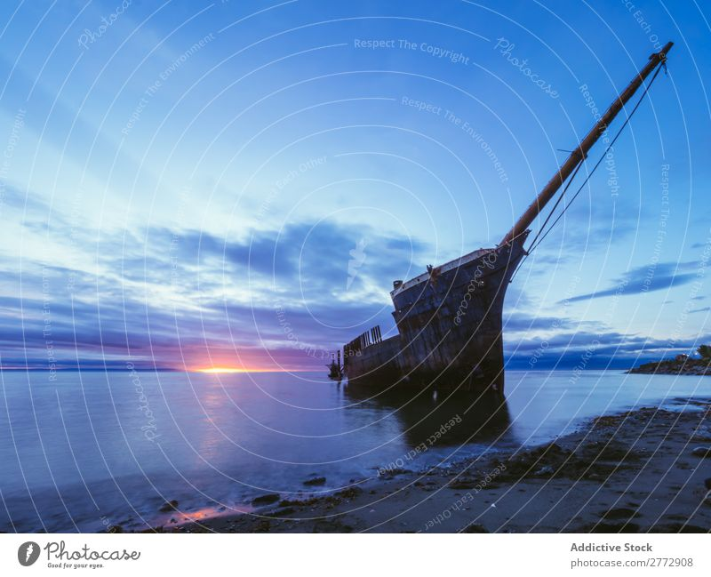 Wrecked ship in sunset time Watercraft Coast Ocean Landscape Destruction Vacation & Travel
