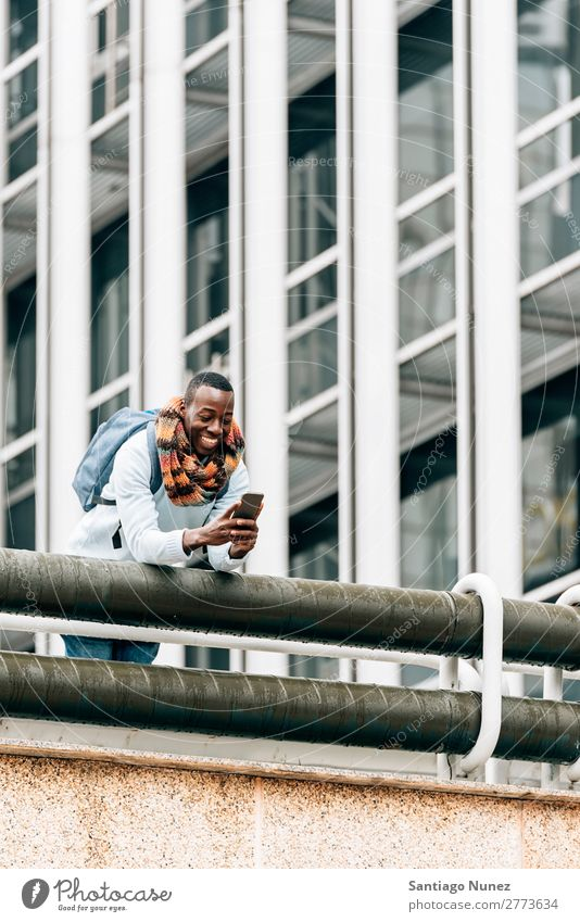 Businessman in the Street. Man Black African American Cellphone Youth (Young adults) Telephone Happy Mobile Exterior shot PDA texting Communication Typing