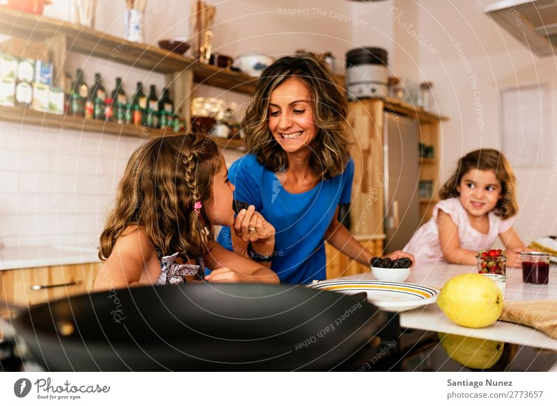 Little sisters cooking with her mother in the kitchen. Mother Child Girl Cooking tasting Kitchen Chocolate Ice cream Daughter Day Happy Joy Family & Relations