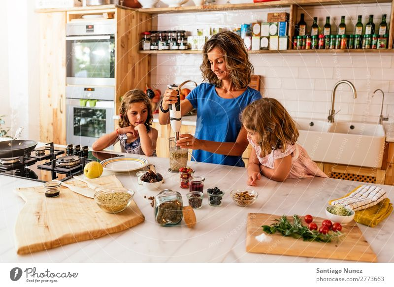 Little sisters cooking with her mother in the kitchen. Mother Child Girl Cooking Kitchen Mixer Tomato