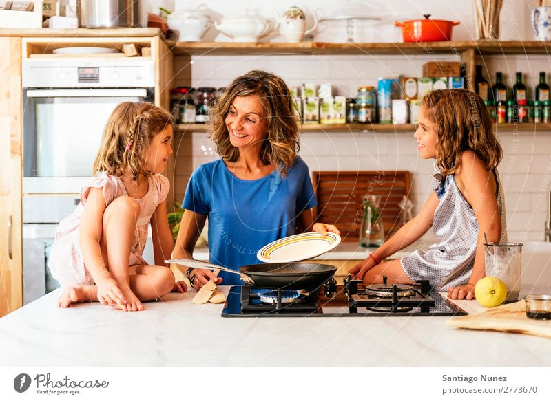 Little sisters cooking with her mother in the kitchen. Mother Child Girl Cooking Kitchen Chocolate Ice cream Daughter Day Happy Joy Family & Relations Love