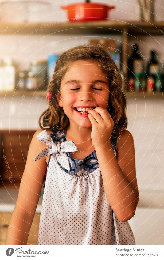 Little girl eating chocolate while preparing baking cookies. Girl Child Nutrition To feed savoring Eating enjoying Portrait photograph Appetite Smiling Laughter