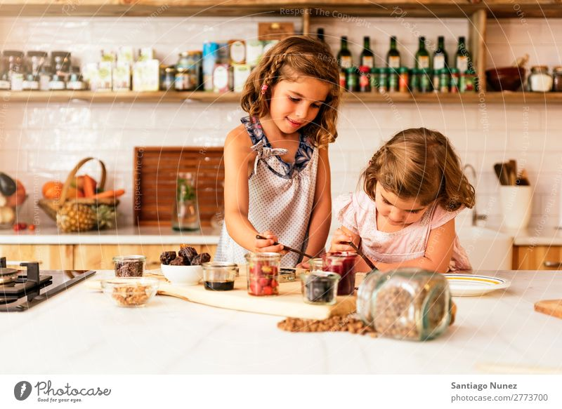 Little sisters girl preparing baking cookies. Girl Child Nutrition Portrait photograph Cooking Kitchen Appetite Preparation Make Smiling Laughter Lunch Baby