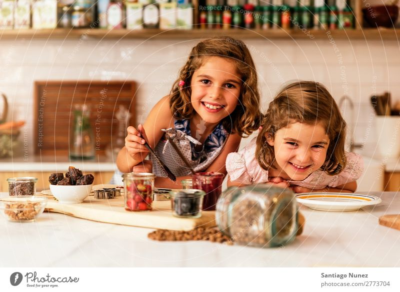 Little sisters girl preparing baking cookies. Child Girl Cooking Kitchen Chocolate Flour Dirty stained Laughter Daughter Day Happy Joy Playing