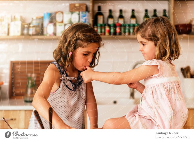 Little sisters girl preparing baking cookies. Child Girl Cooking Kitchen Chocolate tasting savoring Fingers Ice cream Strawberry Daughter Day Happy Joy