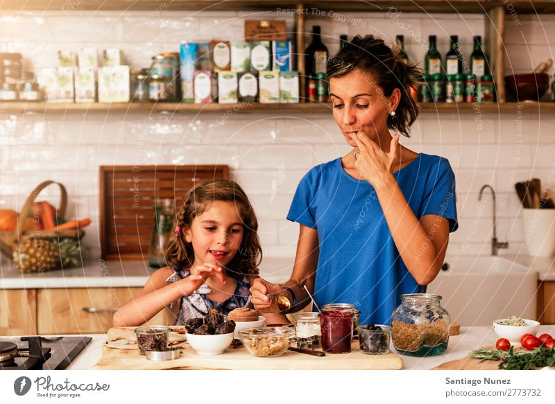 Little girl cooking with her mother in the kitchen. Mother Girl Cooking Kitchen Chocolate Daughter