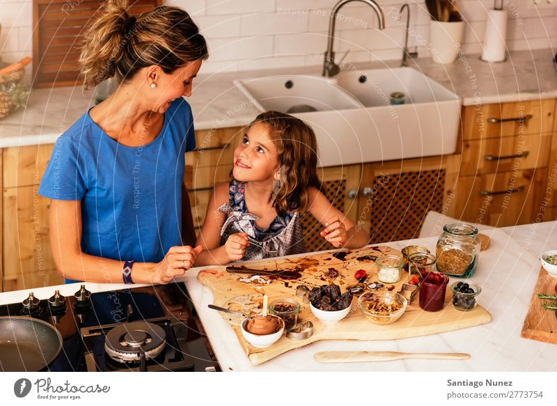 Little girl cooking with her mother in the kitchen. Mother Girl Cooking Kitchen Chocolate Ice cream Daughter Day Happy Joy Family & Relations Love Baking Food