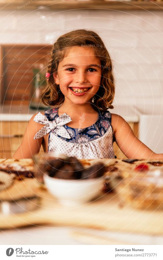 Portrait of little girl preparing baking cookies. Girl Child Nutrition Chocolate To feed savoring Eating enjoying Portrait photograph Appetite Smiling Laughter