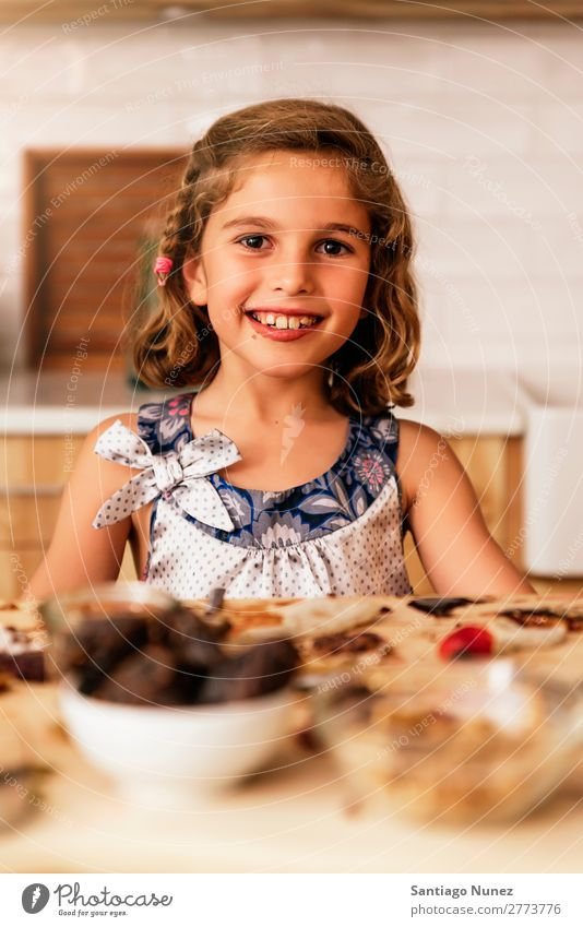 Portrait of little girl preparing baking cookies. Girl Child Nutrition To feed savoring Eating enjoying Portrait photograph Appetite Smiling Laughter Lunch Baby