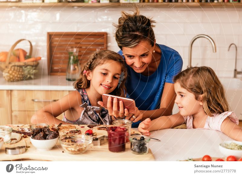 Little sisters cooking with her mother in the kitchen. Mother Child Girl Cooking Kitchen Chocolate Mobile PDA using app Solar cell recipe Daughter Day Happy Joy
