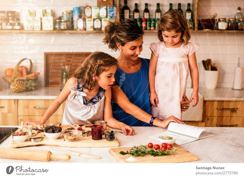 Little sisters cooking with her mother in the kitchen. Mother Child Girl Cooking Kitchen Tomato Pizza Vegetable Daughter Spread Day Happy Joy Family & Relations