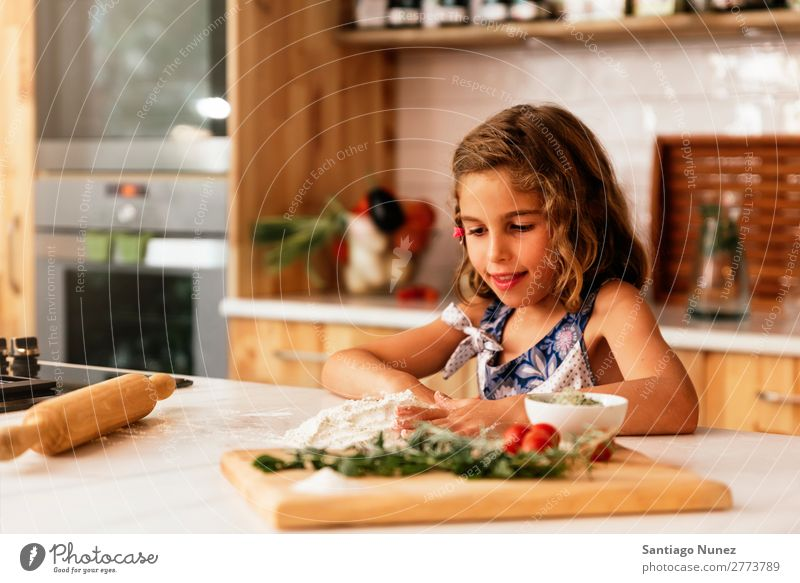 Portrait of little girl preparing baking cookies. Girl Child Nutrition Portrait photograph Cooking Kitchen Bakery Baking Appetite Preparation Make Smiling