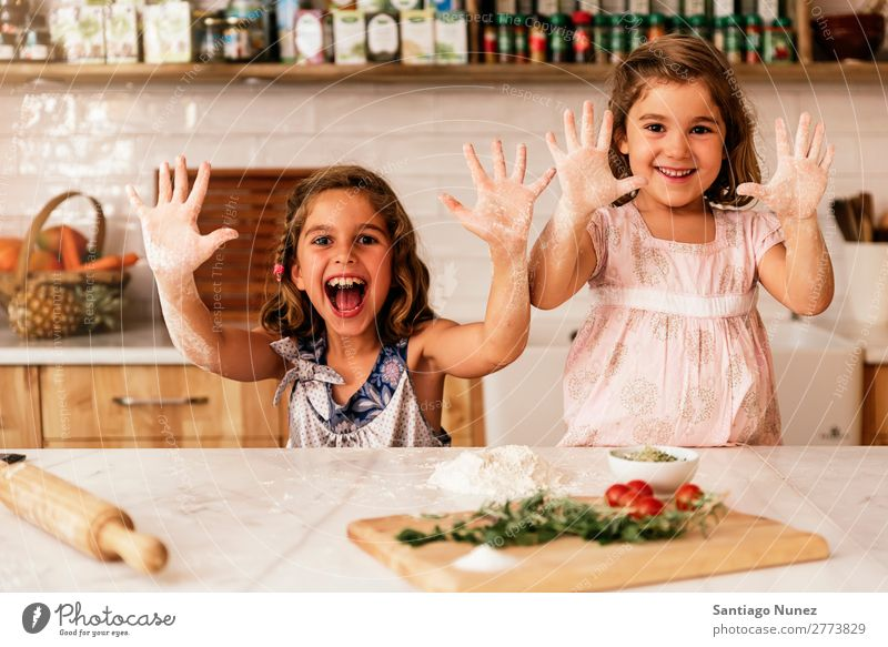 Little sisters girl preparing baking cookies. Child Girl Cooking Kitchen Chocolate Flour Hand Dirty stained Laughter Daughter Day Happy Joy Playing