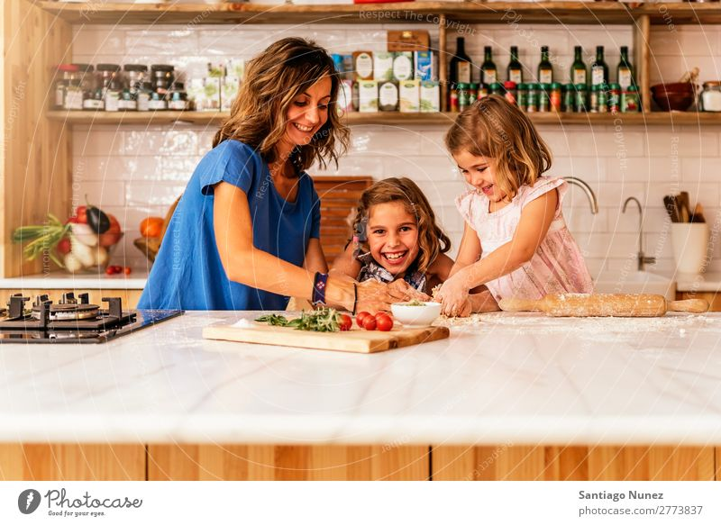 Little sisters cooking with her mother in the kitchen. Mother Child Girl Cooking Kitchen Crêpe Pizza Vegetable Daughter Spread Day Happy Joy Family & Relations