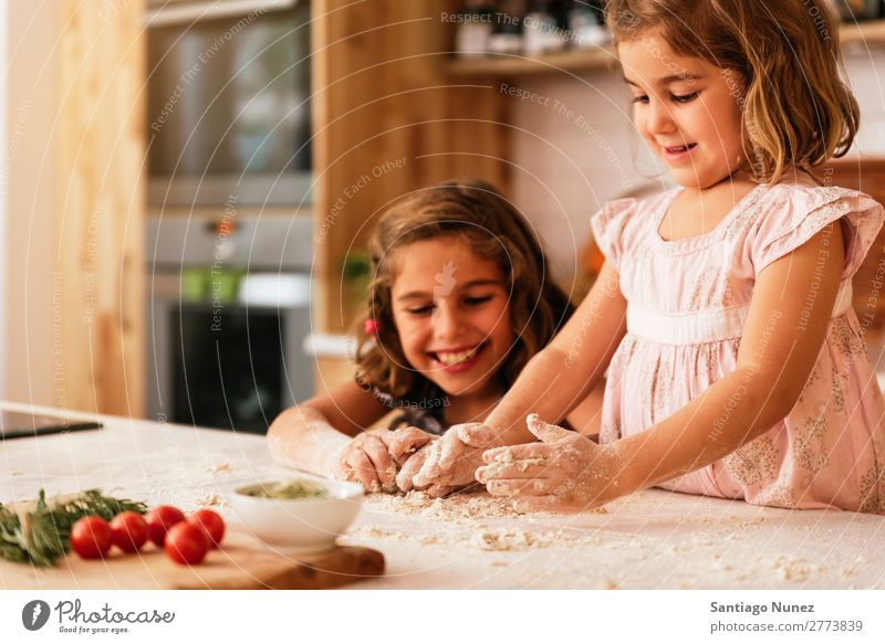 Little sisters kneading dough preparing for baking cookies. Child Girl Cooking Kitchen Flour Hand Dough Dirty stained Laughter Daughter Day Happy Joy Playing