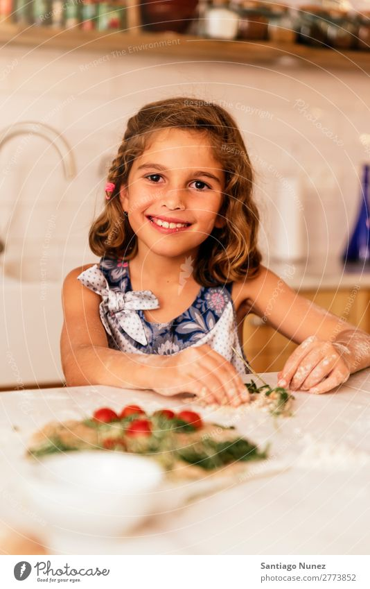 Portrait of little girl preparing baking cookies. Girl Child Nutrition To feed savoring Eating enjoying Flour Dough Portrait photograph Appetite Smiling