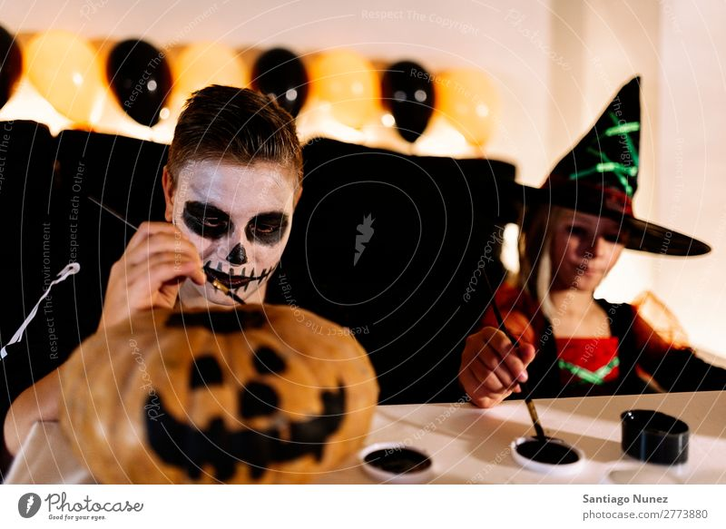 Happy children disguised decorating a pumpkin at home. Hallowe'en Child Girl Boy (child) Painting (action, artwork) Skeleton Witch Disguised Joy