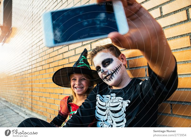 Happy children disguised taking photo with phone in the street. Hallowe'en Child Girl Boy (child) Selfie Skeleton Disguised Mobile PDA Photography Telephone