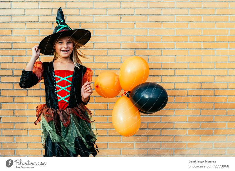 Portrait of beautiful girl disguised of witch in the street. Hallowe'en Child Girl Painting (action, artwork) Disguised Witch Joy Family & Relations Sister