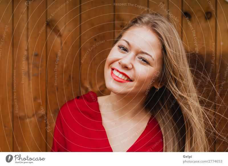 Happy blonde girl with red clothes and lips Lifestyle Beautiful Hair and hairstyles Make-up Human being Woman Adults Lips Plant Jacket Blonde Wood Smiling