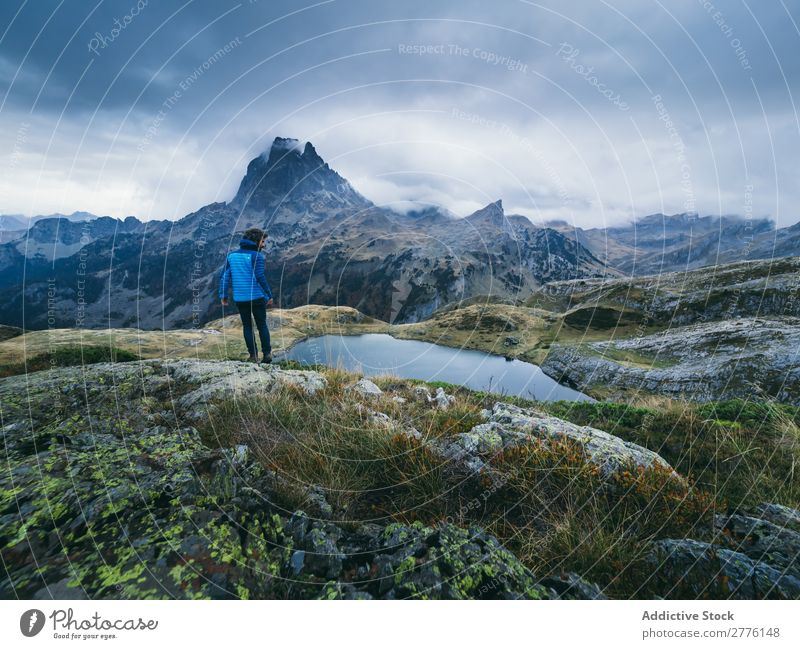 Traveler posing alone in mountains Human being traveler Clouds Mountain Dream Range Panorama (Format) tranquil Nature Lake Mysterious exploration
