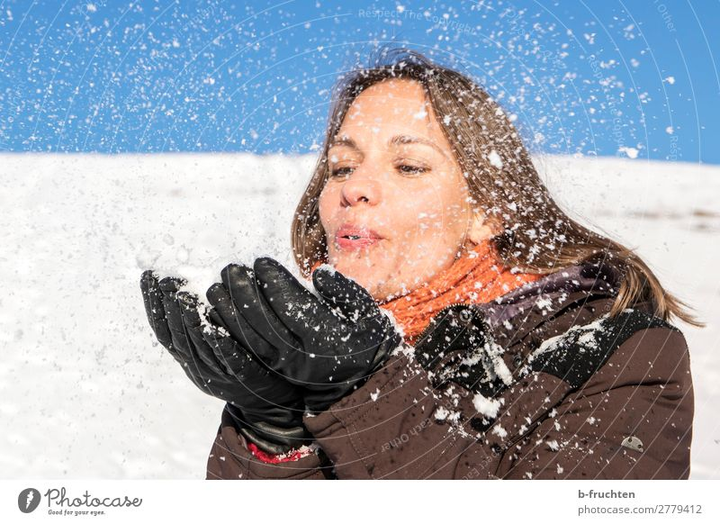 Woman blowing snow from her hands Adults Face Hand Fingers 1 Human being Winter Snow Coat Scarf Happiness Joy Contentment Joie de vivre (Vitality) Sympathy