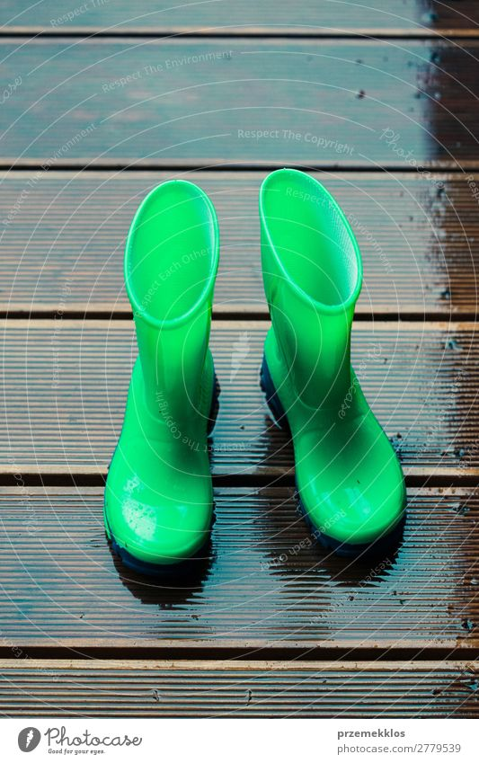 Rain boots standing on a wooden porch while raining Joy Summer Child Human being Woman Adults Man Weather Coat Footwear Boots Rubber boots Small Wet Cute Green