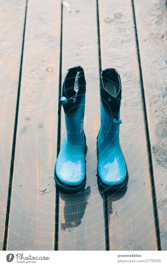 Rain boots standing on a wooden porch while raining Woman Child Human being Man Summer Green Joy Adults Small Weather Footwear Wet Cute Seasons Checkered